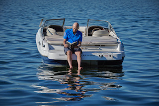 Ward reading on his boat and in front of his house on Lake Monona.